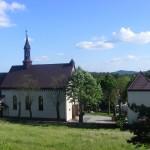 Widok na kościół parafialny i dzwonnicę ze wzniesienia za organistówką